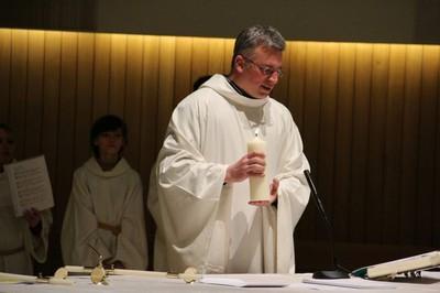 Ein Gebet wird mit einer brennenden Kerze in Hand vorgetragen.